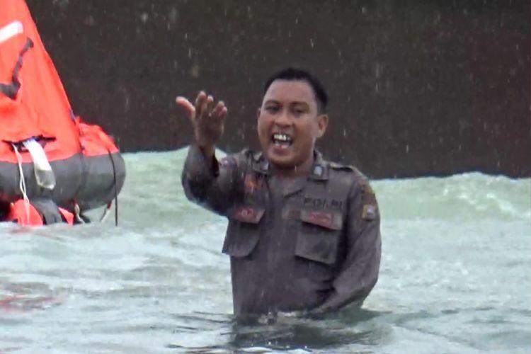 Bripka Faisal saat menyelamatkan penumpang kapal yang kandas.