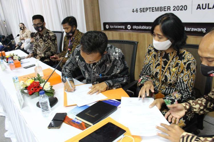 Ketua KPU Karawang Miftah Farid tengah menandatangani berkas saat pendaftran bakal calon Bupati dan Wakil Bupati Karawang periode 2020-2025, Jumat (4/9/2020).