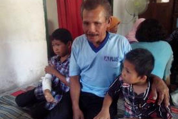 Ilham Nuralim (tangan diperban) bersama anggota keluarganya sedang menunggu kedatangan jenazah Suniyem. Mereka adalah satu keluarga asal Desa Bangsongan, Kecamatan Kayen Kidul, Kabupaten Kediri, yang menjadi korban dalam kecelakaan bis yang terjadi di Waru, Sidoarjo, Senin (13/10/2014).
