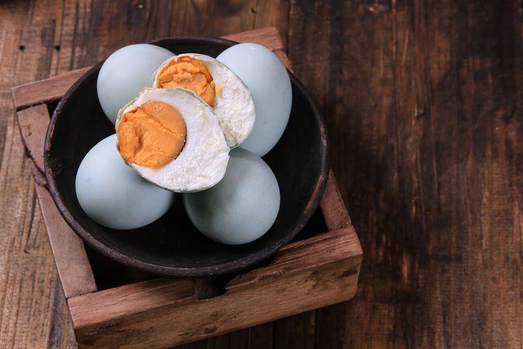 Ilustrasi telur asin di dalam mangkuk.