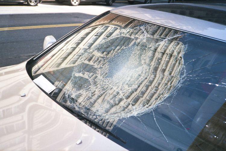 Kaca mobil pecah akibat lemparan batu.