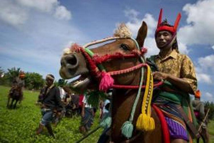 Para pria mengikuti tradisi Pasola, perang di atas kuda di Desa Ratenggaro, Sumba, NTT, 22 Maret 2014. Pasola dirayakan untuk menyambut masa panen. Biasa dilakukan untuk memulai masa tanam.