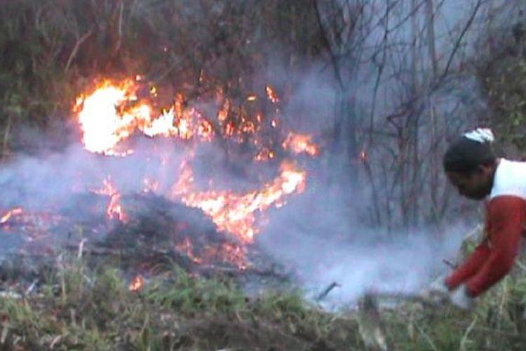 Warga mencoba memadamkan api di lereng Gunung Lawu.