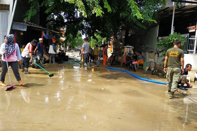 Warga dan staf Pemerintah Kota Bekasi kerja bakti membersihkan lumpur sisa banjir yang masih memenuhi jalan-jalan Perumahan Kemang Ifi, Jatiasih, Kota Bekasi, selepas berakhirnya masa tanggap darurat bencana banjir, Rabu (15/1/2020).