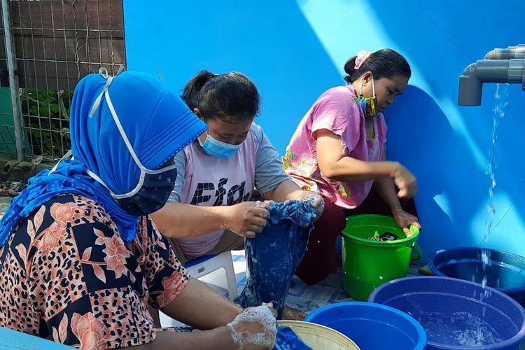Warga setempat mencuci di fasilitas cuci umum yang dibuka di kawasan RW 09, Pegadungan, Kalideres, Jakarta Barat pada, Jumat (30/4/2021).