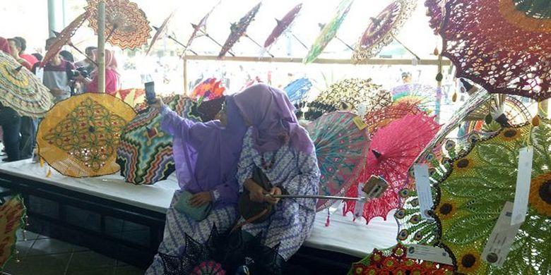 Dua orang wanita berfoto di stan payung rajut di Festival Payung 2017 di Pura Mangkunegaran Solo, Jawa Tengah, Minggu (17/9/2017).
