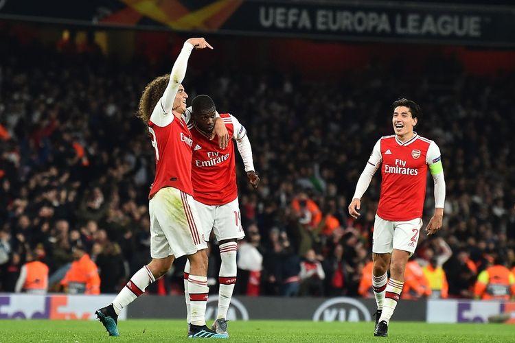 Para pemain Arsenal, Matteo Guendouzi dan Hector Bellerin, merayakan gol yang dicetak Nicolas Pepe saat melawan Vitoria de Guimaraes pada ajang Liga Europa 2019-2020. (Photo by Glyn KIRK / AFP)