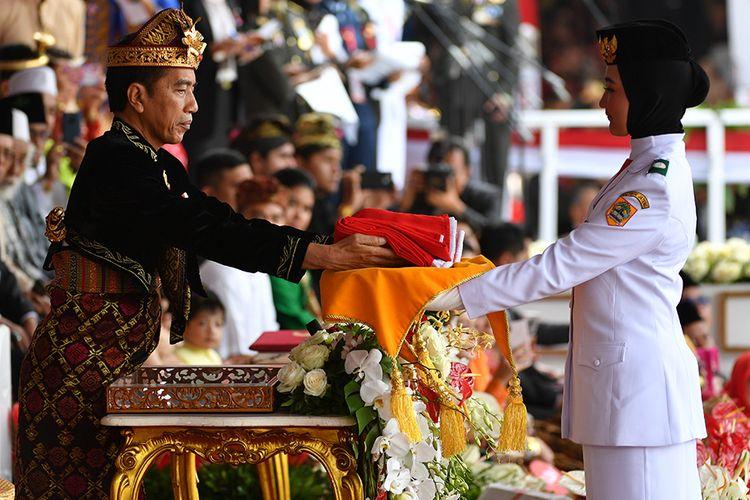 Presiden Joko Widodo menyerahkan bendera kepada Pasukan Pengibar Bendera Pusaka (Paskibraka) saat Upacara Peringatan Detik-Detik Proklamasi 1945 di Istana Merdeka, Jakarta, Sabtu (17/8/2019). Peringatan HUT RI tersebut mengangkat tema SDM Unggul Indonesia Maju.