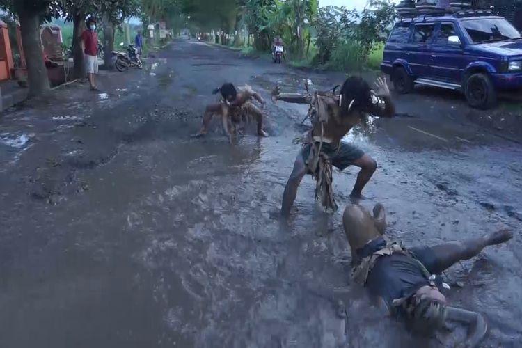 Tiga orang melakukan aksi menari tarian celeng, di ruas jalan yang berlubang di Trenggalek Jawa Timur,