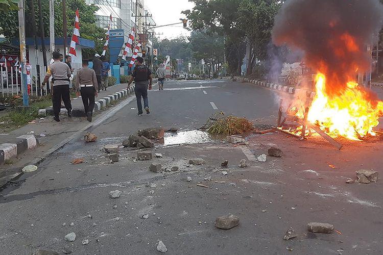 Warga pengunjuk rasa turun ke jalan dan berhadapan dengan aparat keamanan di Manokwari, Papua, Senin (19/8/2019). Aksi yang diwarnai kericuhan itu terjadi menyusul protes penangkapan mahasiswa Papua di sejumlah wilayah di Jawa Timur.