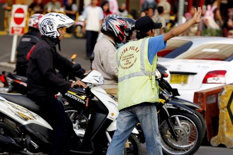 Warga atau kerap disebut dengan polisi cepek mengatur lalu lintas kendaraan di dekat pusat perbelajaan Cililitan, Jakarta Timur, Selasa (2/11/2010). Meski tidak meminta namun kebanyakan pengguna kendaraan roda empat kerap memberinya uang receh.