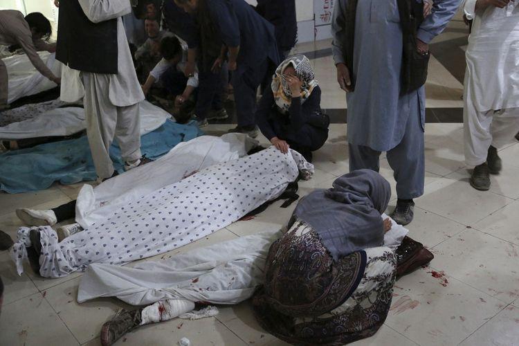 Keluarga dan kerabat berduka di samping jenazah korban tewas ledakan bom di sekolah sebelah barat Kabul, Afghanistan, pada 8 Mei 2021. Terdapat 40 korban tewas dalam insiden yang belum diketahui siapa kelompok yang bertanggung jawab.