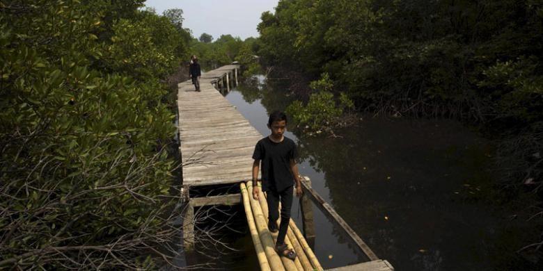 Warga berhati-hati melewati titian bambu di Jembatan Pelangi, Pulau Lancang, Kepulauan Seribu, Minggu (18/10/2015). Jembatan yang masih dalam proses pembangunan itu nantinya akan dibuat mengitari hutan bakau di bagian barat Pulau Lancang.