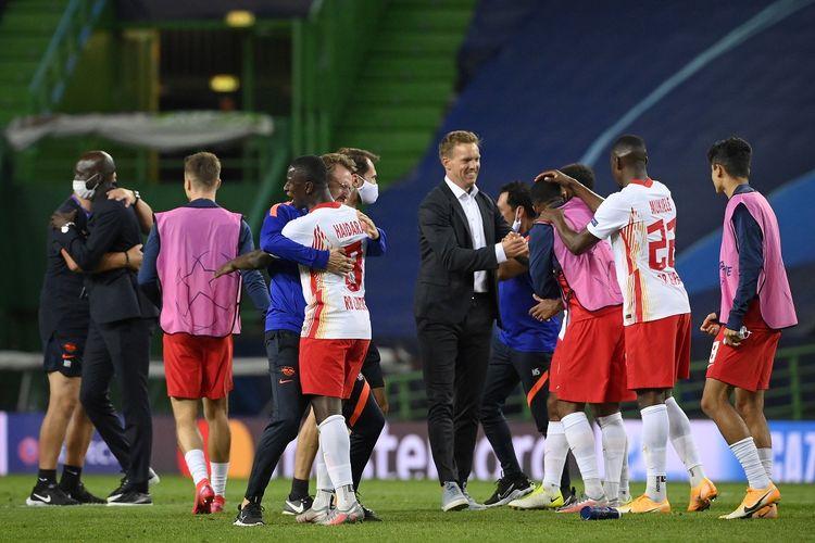 Pelatih kepala Leipzig Jerman Julian Nagelsmann (tengah) dan para pemainnya merayakan kemenangan mereka di akhir pertandingan sepak bola perempat final Liga Champions UEFA antara Leipzig dan Atletico Madrid di stadion Jose Alvalade di Lisbon pada 13 Agustus 2020.
