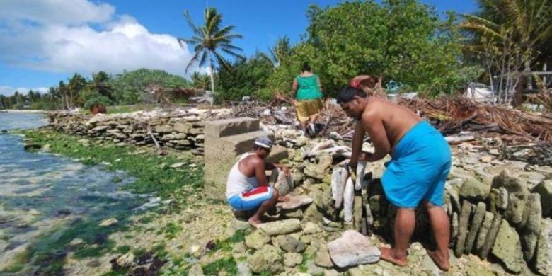 Foto ini menampilkan warga pulau Kiritimati, Kiribati tengah membangun tembok laut untuk mengurangi dampak ombak samudera Pasifik ke daratan. Kiribati adalah negara kepulauan kecil di Pasifik yang ketinggian rata-rata wilayah daratnya hanya beberapa meter di atas permukaan air laut. Akibat perubahan iklim, permukaan air laut meningkat dan membahayakan kehidupan di pulau-pulau kecil semacam Kiribati.