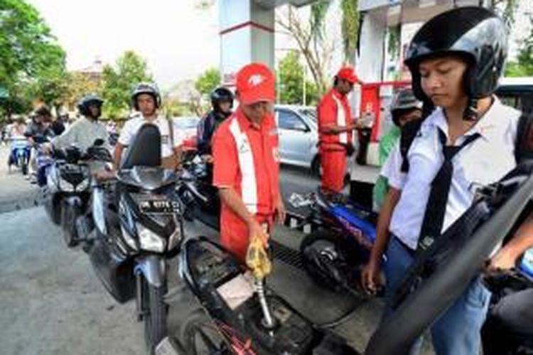 Pengendara motor mengantre di SPBU untuk mengisi bahan bakar minyak (BBM) jenis premium, di Bali, Selasa (26/8/2014). Kelangkaan BBM mulai muncul di beberapa daerah menyusul wacana kenaikan harga BBM karena komsumsi BBM melebihi batas maksimal 46 juta kiloliter.