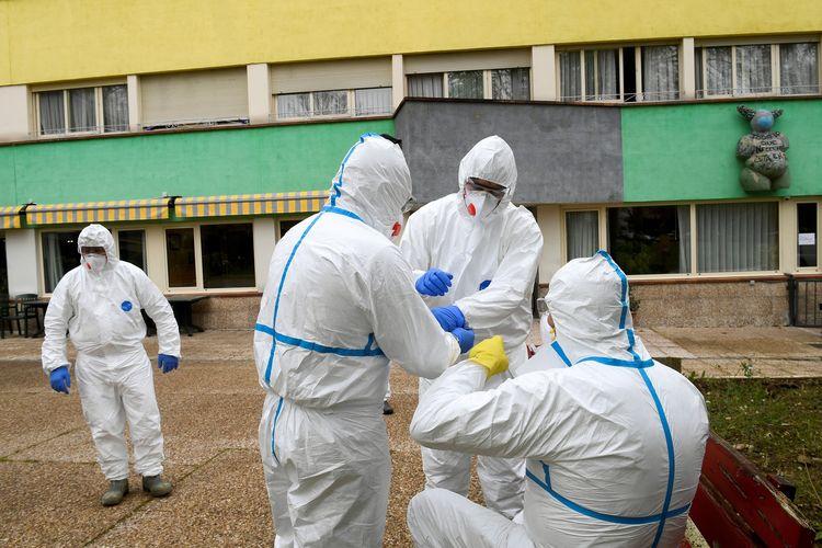 Petugas kebersihan bersiap membersihkan sebuah kompleks apartemen di mana seorang perempuan meninggal, dan sejumlah warga diketahui positif mengidap virus corona di Grado, Asturias, Spanyol, pada 20 Maret 2020.