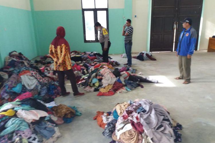 Petugas dari Polres Kobar didampingin aparatur desa memeriksa ribuan potong pakaian perempuan yang terdiri dari berbagai jenis, Rabu (22/7/2020). Ribuan potong pakaian tersebut adalah barang bukti kasus pencurian unik di Desa Natai Baru, Kotawaringin Barat, Kalimantan Tengah.