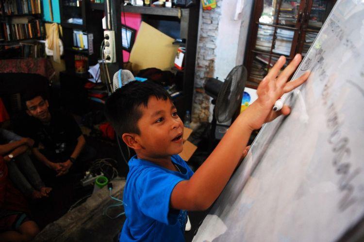 Seorang anak sedang belajar di sanggar Ruang Kreatifitas Anak Tanah Ombak, Kampung Purus 3, Padang, Sumatera Barat, Minggu (16/7/2017). Mayoritas anak-anak di kampung itu tidak dapat menikmati akses pendidikan yang lengkap dikarenakan keterbatasan ekonomi orangtuanya.