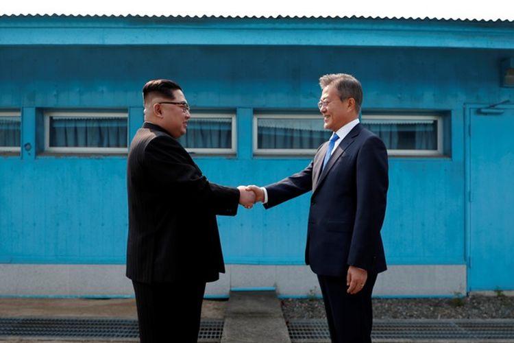 Pemimpin Korea Utara Kim Jong Un (kiri) berjabat tangan dengan Presiden Korea Selatan Moon Jae-in saat bertemu di Garis Demarkasi Militer, di desa perbatasan Panmunjom, Jumat (27/4/2018).