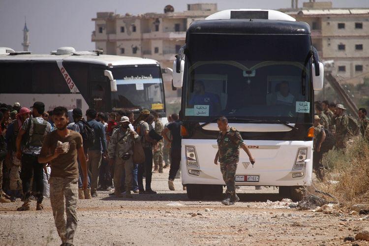 Anggota pasukan pemberontak menaiki bus yang akan membawa mereka meninggalkan wilayah Daraa setelah tercapai kesepakatan dengan pemerintah rezim Suriah.
