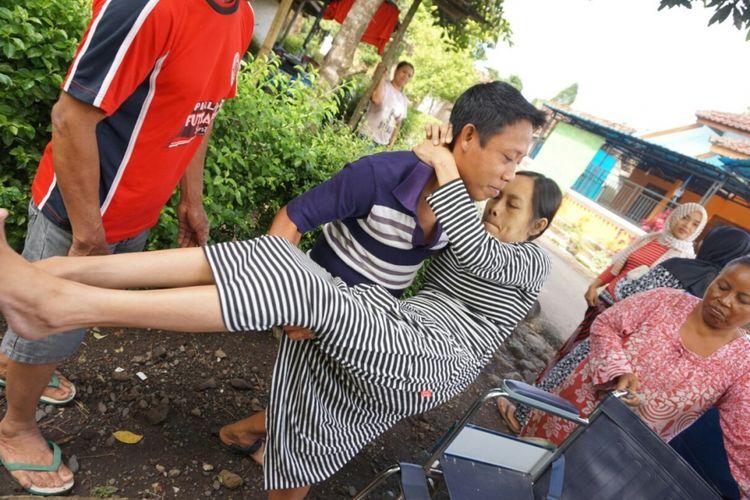 Sugianto saat menggendong istrinya saat akan kontrol ke rumah sakit
