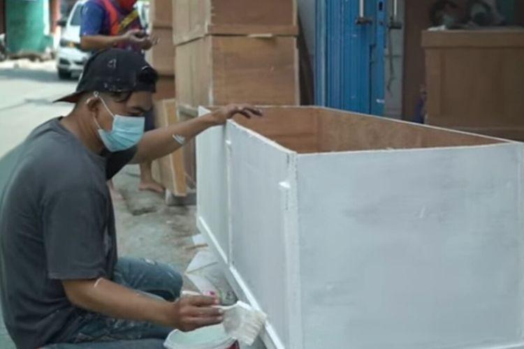 Seorang pekerja sedang mengerjakan produksi pembuatan peti mati untuk jenazah pasien Covid-19 di sentra milik Ibrahim Askar, Kota Bogor, Jawa Barat.