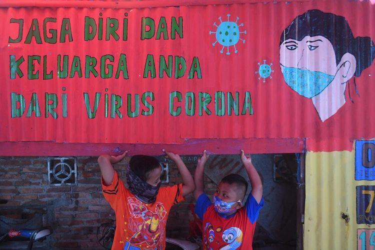 Seorang anak bermain di samping mural bertema COVID-19 di Jakarta, Senin (27/7/2020). Berdasarkan data dari Satgas Penanganan COVID-19 per 27 Juli 2020, kasus positif COVID-19 di Indonesia telah mencapai 100.303 kasus, dimana 58.173 orang dinyatakan sembuh dan 4.838 orang meninggal dunia. ANTARA FOTO/Akbar Nugroho Gumay/pras.