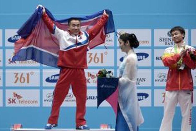 Atlet angkat besi Korea Utara, Om Yun Chol (kiri), mengangkat bendera saat merayakan kemenangannya di nomor 56 kg pada Asian Games 2014 di Incheon, Korea Selatan, Sabtu (20/9/2014).