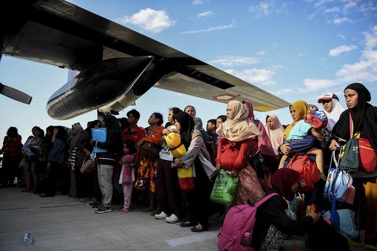 Warga antre untuk dievakuasi menggunakan pesawat Hercules di Bandara Mutiara Sis Al Jufri Palu, Sulawesi Tengah, Minggu (30/9/2018). Sejumlah warga Palu dievakuasi ke luar Kota Palu menggunakan pesawat Hercules karena susahnya mencari makan pascagempa dan tsunami di Palu.