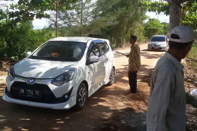 Wisatawan masuk Pantai Pukan, Bangka, dengan menyumbang uang secara sukarela, Minggu (16/6/2019).