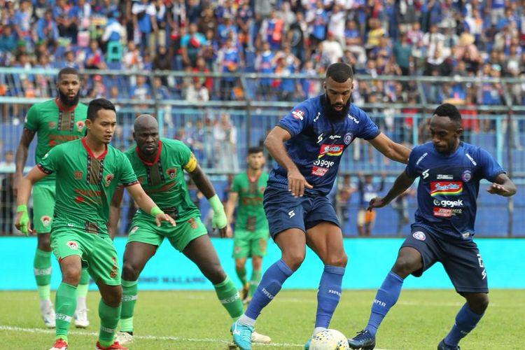 Pemain Arema FC ketika sedang berhadapan dengan pemain Kalteng Putra