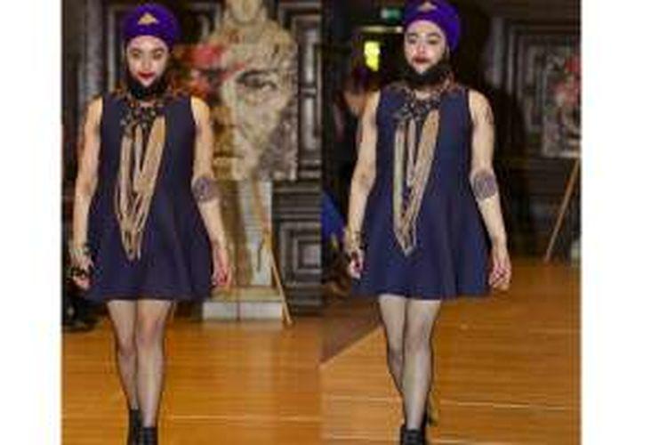 Harnam Kaur melenggang sebagai model di panggung runway mengenakan busana terusan selutut yang anggun.