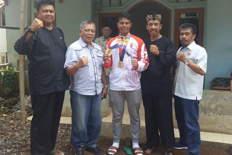 Muahammad Taufik (32) atlet asal Kabupaten Tasikmalaya yang meraih medali emas di Sea Games Filiphina bersama Koni dan pejabat daerah setempat di rumahnya, Selasa (10/12/2019).