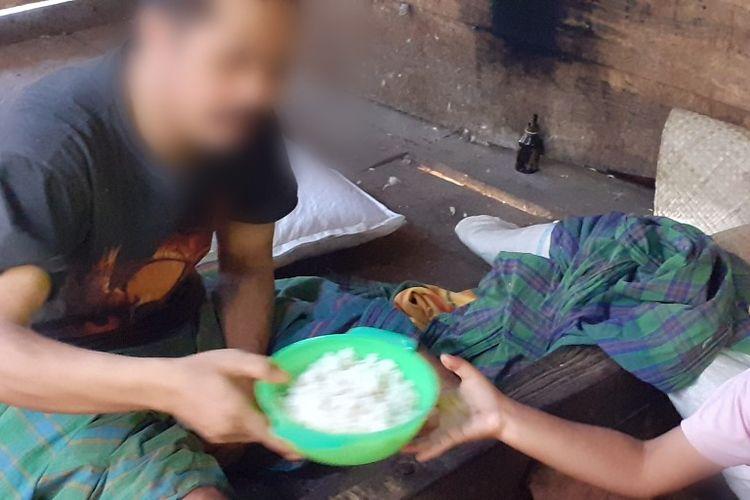 Yohana Grestiara Samur (7), sedang membawa makanan bagi ayahnya yang di pasung di bagian dapur di rumah orangtuanya di Kampung Waegerek, Desa Lidi, Kec. Ranamese, Kab. Manggarai Timur, Flores, NTT, Minggu, (17/11/2019). (KOMPAS.com/MARKUS MAKUR)( KOMPAS.com/MARKUS MAKUR)