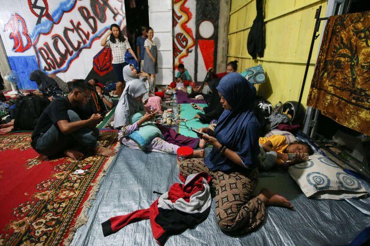 Warga tidur di luar rumah pasca gempa di Kota Pasangkayu, Sulawesi Barat, Sabtu (29/9/2018). Akibat gempa berkekuatan magnitudo 7,4 yang mengguncang wilayah Donggala, Sulawesi Tengah, Jumat (28/9/2018) mengakibatkan korban jiwa, kerusakan, dan tsunami yang menerjang Donggala dan Palu.