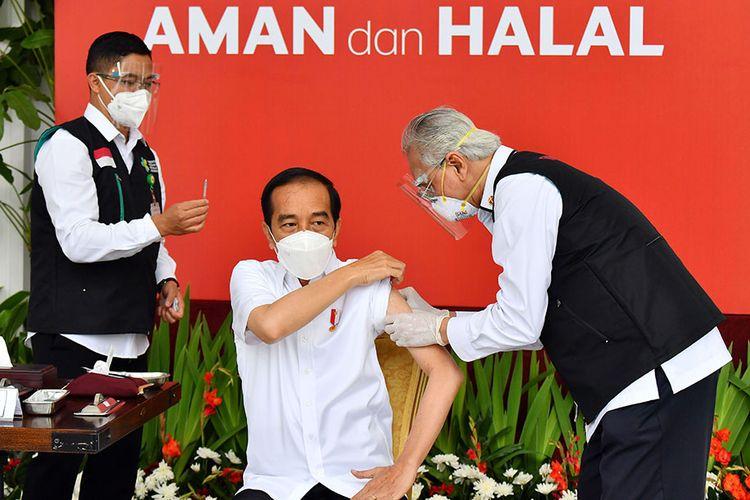 Presiden Joko Widodo (tengah) bersiap disuntik dosis pertama vaksin COVID-19 produksi Sinovac oleh vaksinator Wakil Ketua Dokter Kepresidenan Prof Abdul Mutalib (kanan) di beranda Istana Merdeka, Jakarta, Rabu (13/1/2021). Penyuntikan perdana vaksin COVID-19 ke Presiden Joko Widodo tersebut menandai dimulainya program vaksinasi di Indonesia. ANTARA FOTO/HO/Setpres-Agus Suparto/wpa/wsj.