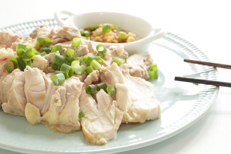 Ilustrasi ayam kukus dengan taburan daun bawang dan jahe.