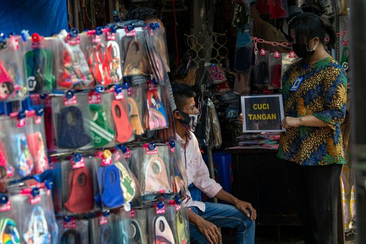 Petugas pengelola pasar melakukan sosialisasi pencegahan COVID-19 dengan membawa poster berisi pesan di Pasar Jatinegara, Jakarta, Kamis (11/6/2020). Upaya tersebut untuk meminimalisir kasus penularan atau penyebaran COVID-19 terjadi di pasar.