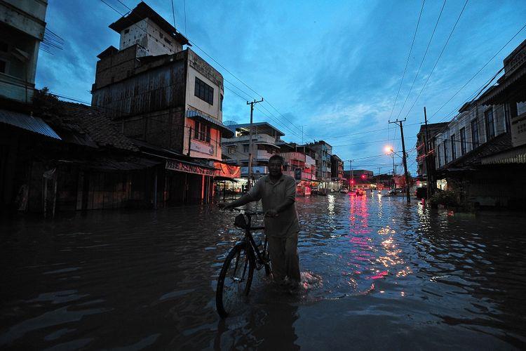 Warga menuntun sepeda saat menerobos banjir yang menggenangi Jalan Orang Kayo Hitam setelah diguyur hujan di Jambi, Senin (12/7/2021). Sejumlah ruas jalan dan permukiman warga di kota itu terendam banjir akibat buruknya sistem drainase. ANTARA FOTO/Wahdi Septiawan/wsj.