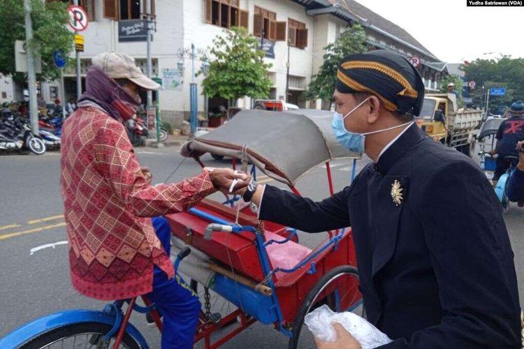 Berbusana adat Jawa dan bermasker, relawan membagikan masker dan hand sanitizer gratis untuk tukang becak, juru parkir, pedagang pasar dan kuli gendong di Paaar Gedhe Solo, 21 Maret 2020.