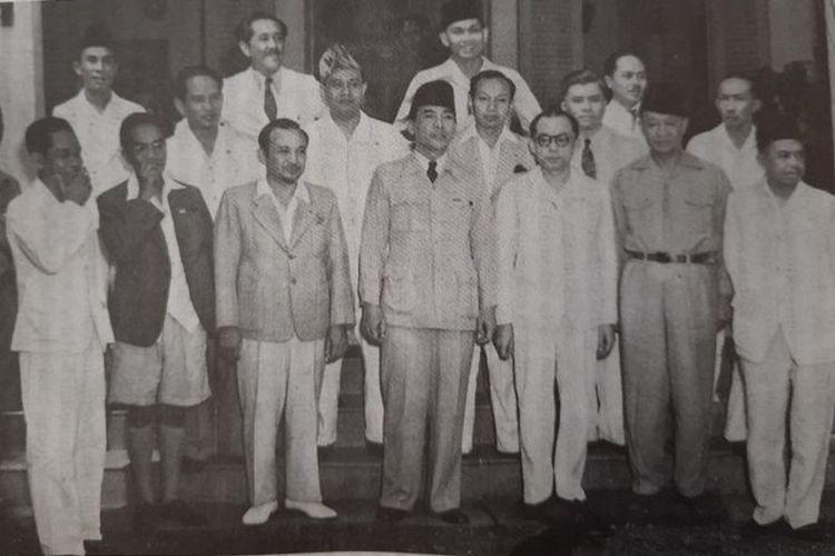 Menteri Penerangan Amir Sjarifuddin (depan, nomor dua dari kiri, mengenakan jas dan bercelana pendek), bersama Presiden Sukarno, Wapres Mohammad Hatta, dan menteri-menteri kabinet pertama, 4 Oktober 1945.