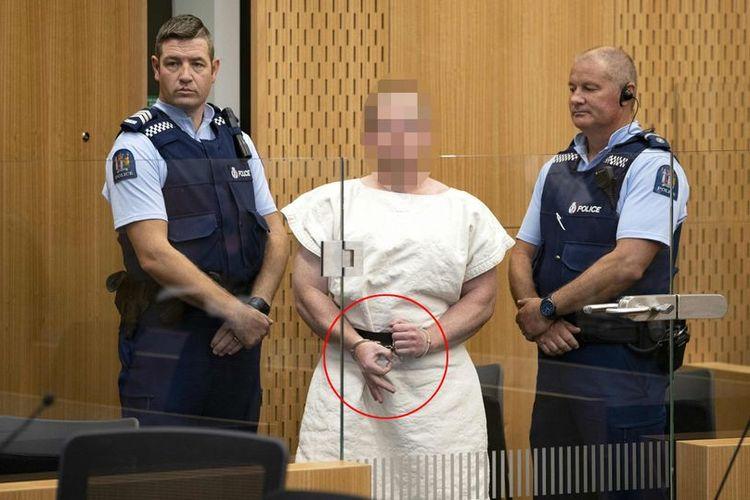 Brenton Tarrant, teroris penembakan masjid Selandia Baru membentuk gestur OK yang merupakan lambang supremasi kulit putih dengan jarinya ketika masuk untuk menjalani sidang perdana Sabtu (16/3/2019).