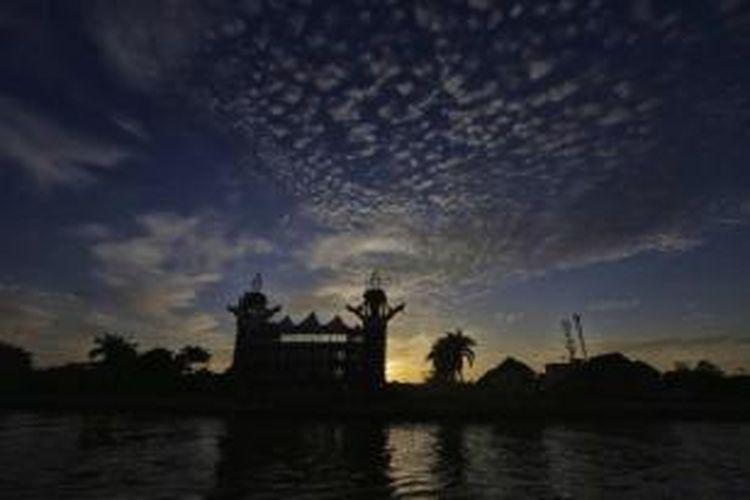 Matahari terbit di siring Sungai Martapura, Kota Banjarmasin, Kalimantan Selatan, tempat diadakannya pasar terapung, 23 Maret 2014. Berbeda dengan pasar terapung lainnya di Kalsel, pasar terapung yang baru ada setahun ini sengaja diadakan tiap minggu pagi berbarengan dengan kegiatan car free day.
