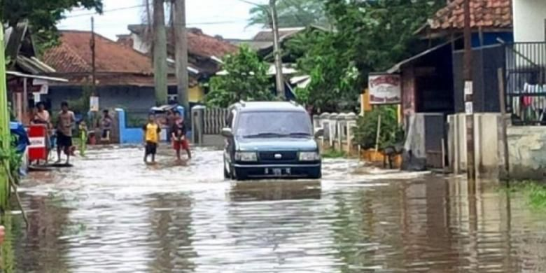 Sebuah mobil mencoba menerobos banjir di kawasan Sapan, Kampung Cikeruh, Desa Tegalluar?, Kecamatan Bojongsoang, Kabupaten Bandung, Rabu (8/3/2017).