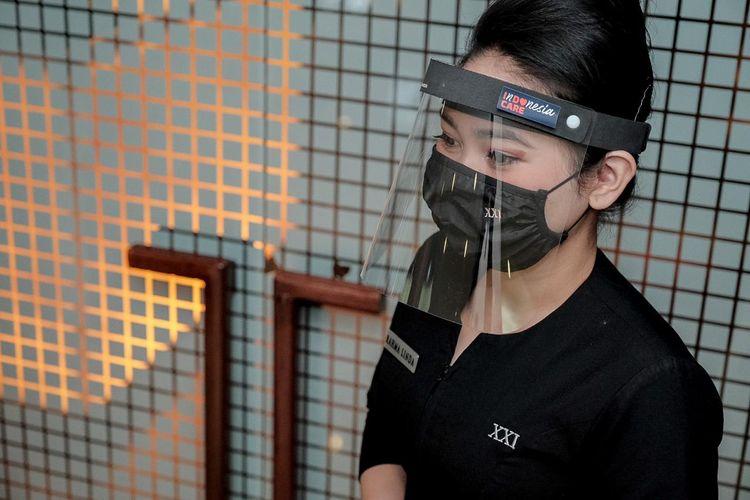 Petugas bioskop mengenakan masker dan face shield