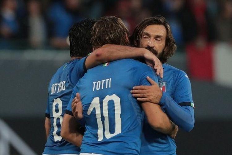 Andrea Pirlo (kanan) memeluk Francesco Totti (tengah).