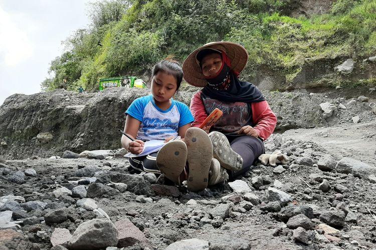 Wanda Hera Kurniawati saat belajar daring didampingi ibunya Sutarti di area pertambangan Kali Gendol, Cangkringan, Sleman