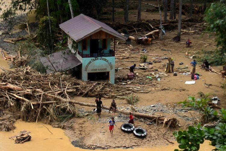 Sejumlah orang membersihkan sisa-sisa kerusakan yang diakibatkan banjir bandang di Sungai Landak di Desa Timbang Lawan, Kecamatan Bahorok, Langkat pada Rabu (18/11/2020) sore. Banjir bandang memporak-porandakan bangunan di kawasan tersebut. Tidak ada korban jiwa namun kerugian materil cukup besar.