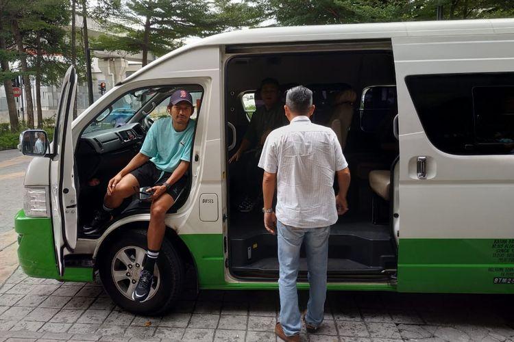 Ibnu Jamil (kiri) duduk di kursi depan dalam bus kecil yang membawa rombongan Puma Indonesia selama berada di Subang Jaya, Malaysia.
